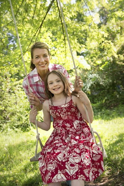 Summer. A girl in a sundress on a swing hung from a tree branch. A mature woman behind her.