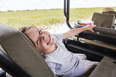 smiling 6 year old boy in safari vehicle, Botswana