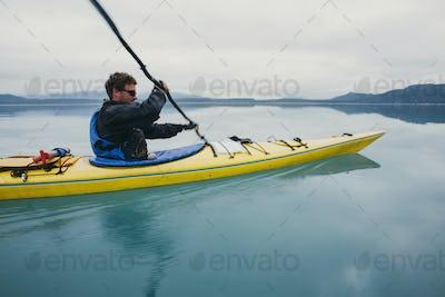 Man sea kayaking inan inlet on the Alaska coastline.