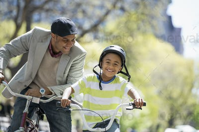 A family in the park on a sunny day. Bicycling and having fun. A father and son side by side.