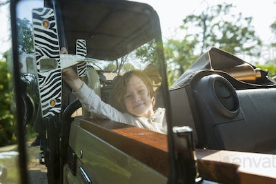 portrait of smiling 6 year old boy in safari vehicle, Botswana
