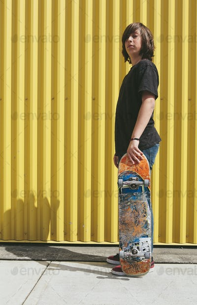 Teenage boy posing with skateboard in front of urban warehouse
