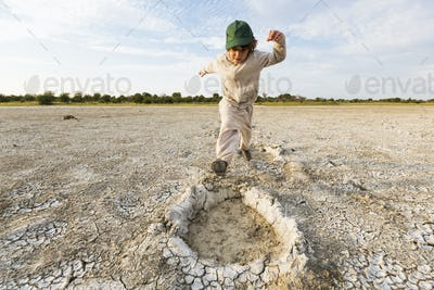 6 year old boy leaping into elephant footprints, Nxai Pan, Botswana