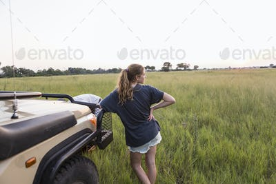 13 year old girl leaning on safari vehicle, Botswana