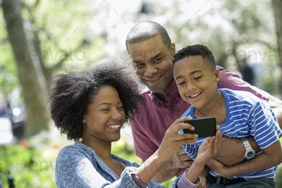 A family in the park. Two adults and a young boy taking photographs with a smart phone.