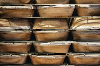Artisan bakery making special sourdough bread, proving baskets on racks.