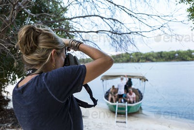 A woman taking photographs of a boat with passengers on the Zambezi River, Botswana