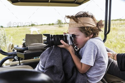6 year old boy taking pictures from safari vehicle, Botswana