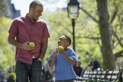 A family in the park on a sunny day.  A man and a boy eating apples.