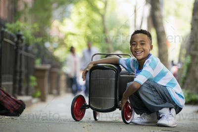 A young boy playing with a old fashioned toy car on wheels on a city street.