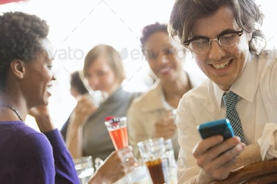 A group of people sitting in a cafe around a table. Men and women checking their smart phones.