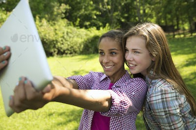 Two girls sitting outdoors on a bench, using a digital tablet.  Holding it out at arm's length.