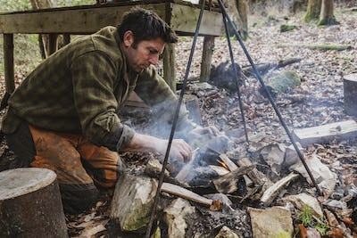 Man starting a camp fire in a forest.