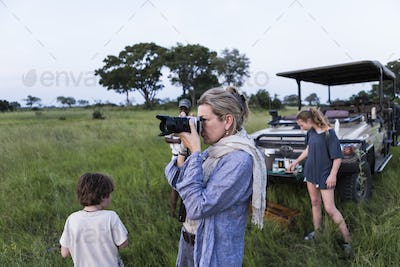 mother taking pictures on safari at sunset, Botswana