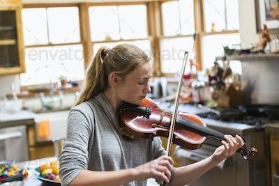13 year old girl playing violin at home