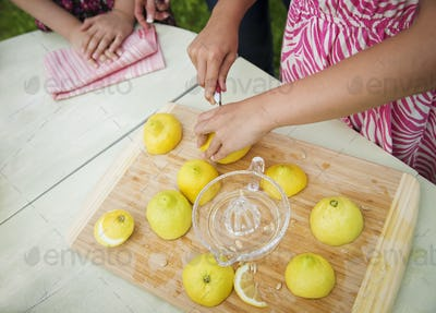 A tabletop chopping board. A child cutting up lemons and juicing them for lemonade.