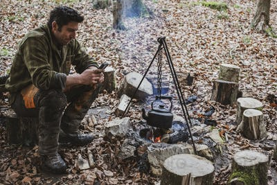 Man sitting by a camp fire in a forest, boiling kettle of water.