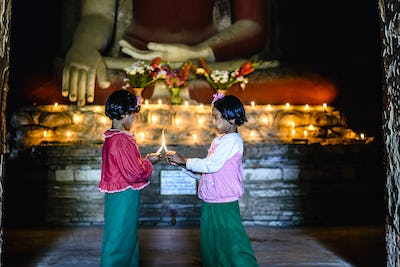 55054,Asian girls lighting candles in Buddhist temple