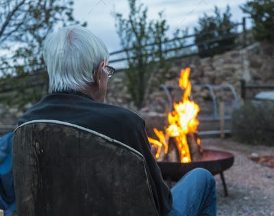 Rear view of an elderly man seated looking at logs burning in a firepit