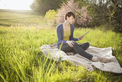 A young woman sitting in a grass field on a blanket, holding a digital tablet.