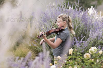 Teenage girl standing among flowering roses and shrubs, playing a violin,
