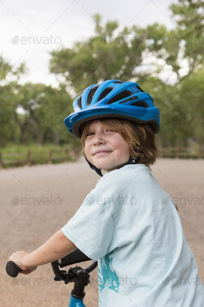 smiling 4 year old boy in a cycle helmet looking over his shoulder.