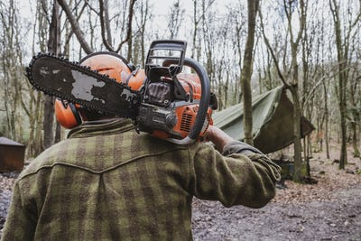 Rear view of man wearing safety gear walking through forest carrying chainsaw on his shoulder.
