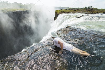 Man in the water at the Devils Pool on the edge of Victoria Falls, looking over the waterfall edge.