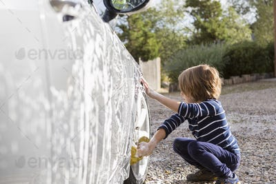 Four year old boy washing a car with cleaner and a cloth