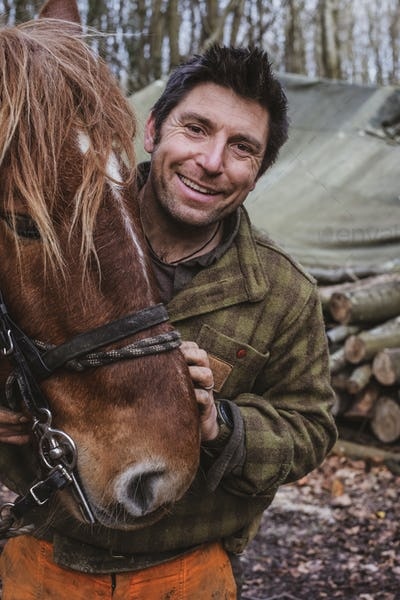 Portrait of a logger with one of his work horses.