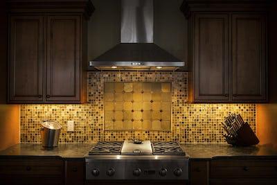 55265,Tile back splash, ventilation hood and stove in dark kitchen