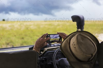 A safari guide taking smart phone picture of approaching storm clouds.