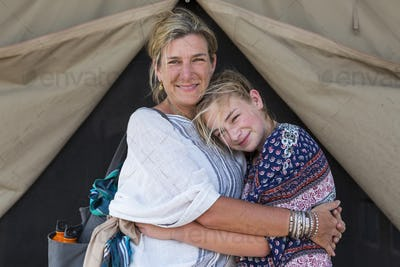 Mother and her young teenage daughter outside a tent.