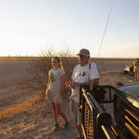 A grandfather and his grand daughter looking out at sunset in the Kalahari Desert