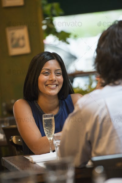 Business people out and about in the city. A couple seated at a table smiling at each other.