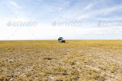 A safari vehicle on open ground in the desert.