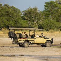 A safari vehicle and passengers close to lions drinking at a water hole.