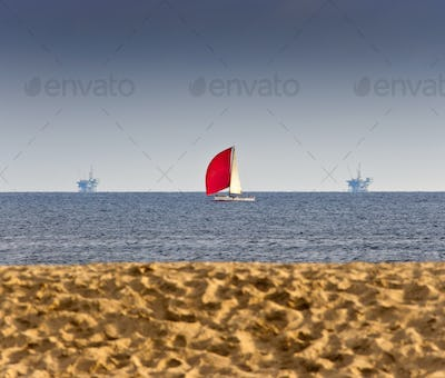 50028,Sailboat and Oil Rigs on the Ocean