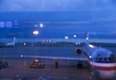 View through an airport window of airport runways and taxiway at dusk.