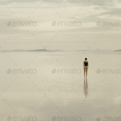 Woman standing on the flooded Bonneville Salt Flats, at dusk.