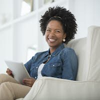 A young woman sitting in an armchair with a digital tablet. An office interior.