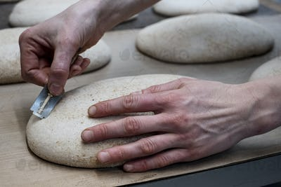 Artisan bakery making special sourdough bread, a baker using a blade to cut into the proving dough.