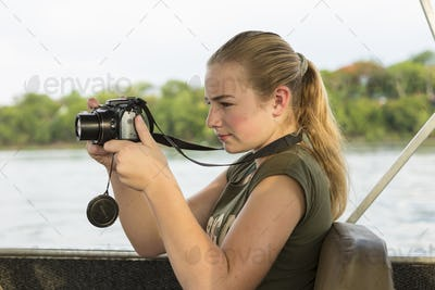 A twelve year old girl using a camera seated in a river boat.