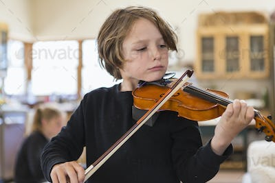 Six year old boy playing violin, having a remote video lesson in lockdown at home.