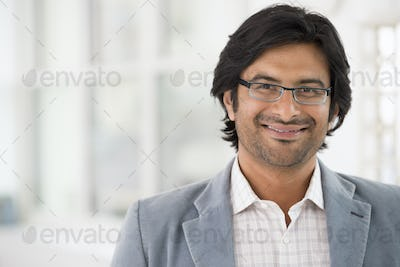 A business man in a light jacket wearing glasses.