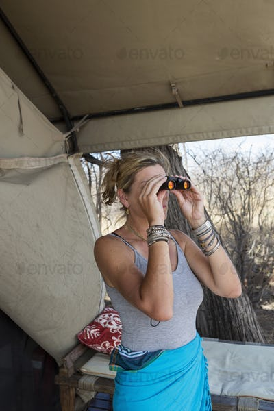Mature woman by a tent in a wildlife reserve camp using binoculars.