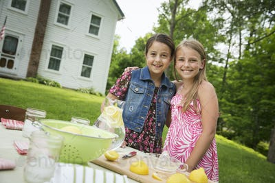 A summer family gathering at a farm. Two children standing side by side. Making homemade lemonade.