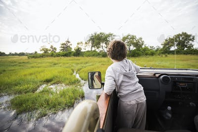 A six year old boy in a safari jeep driving through water in marshes.