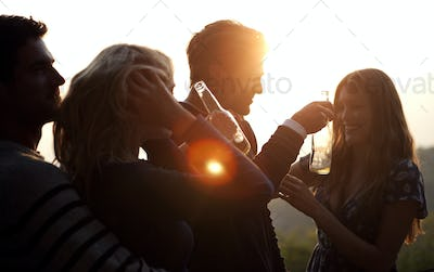 Two men and two women standing outdoors at sunset, holding beer bottles, smiling.