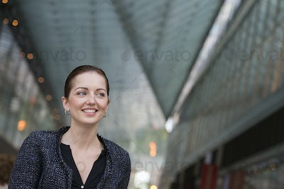 Business people outdoors. A woman in a grey jacket with her hair up, smiling.